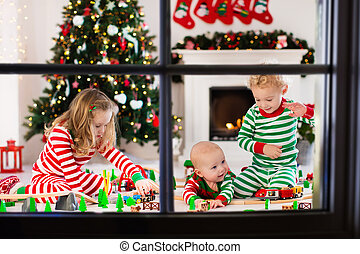 Kids playing with toy railroad on Christmas morning