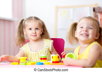 Kids playing with wooden blocks sitting at table in their room