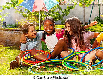 Kids portrait with hula hoops together on grass