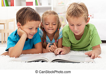Kids practice reading together enjoying a book laying on the...