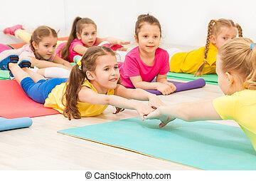 gymnastics coach making bending sideways with kids female