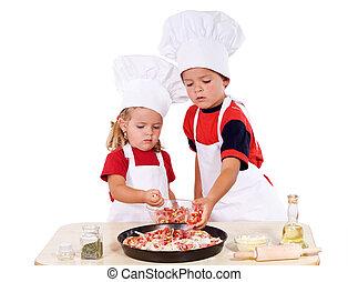 Kids preparing pizza - Two kids dressed as chefs preparing a...