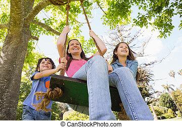 Kids pushing mother on swing