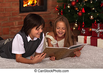 Kids reading a book - in front of the Christmas tree