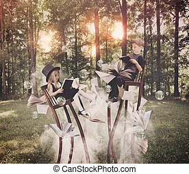 Kids Reading Book in Woods on Long Chairs - Two children are...
