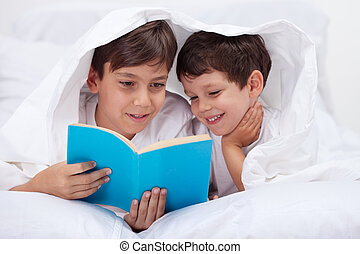 Kids reading under the blanket