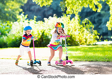 Kids riding scooter in summer park. - Children learn to ride...