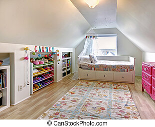 White vaulted ceiling kids room with hardwood floor and rug. Room furnished with single bed, pink antique dresser and storage units for toys