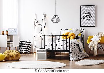 Kids room with yellow pouf - Blanket on yellow chair next to...