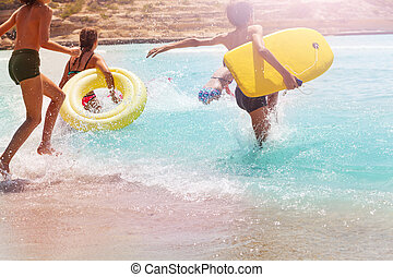 Kids run and jump into the water on sand beach