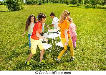 Kids run around playing musical chairs game