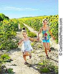 Kids running across sunflower field outdoor. - Group...