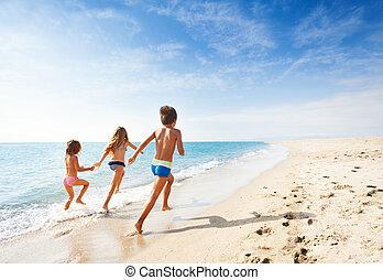 Kids Running Along Beach During Summer Vacation