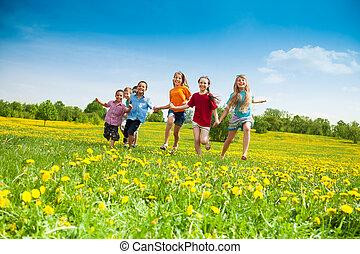 Kids running - Group of happy kids running in the yellow ...
