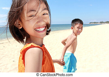 kids running in the beach