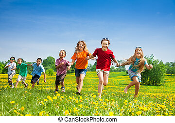 Kids running in the field - Group of seven happy running in ...