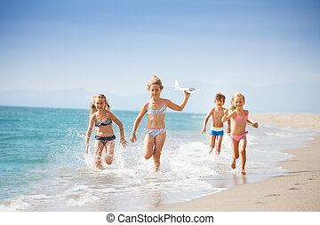 Kids running on coast and playing with toy plane