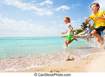 Kids running on the beach water with splashes