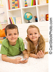 Kids sharing a music player laying on the floor