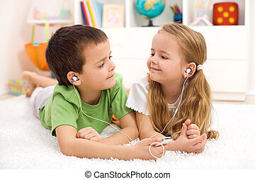 Kids sharing earphones listening to music laying on the ...