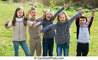 kids showing thumbs up outdoors - Happy friends having fun ...