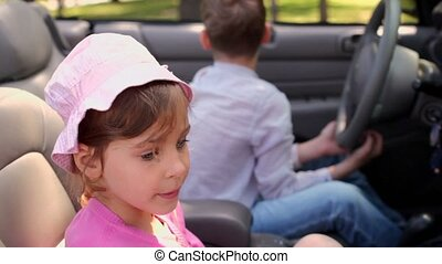 kids sit in cabriolet, boy holds driver wheel, sister blows toy