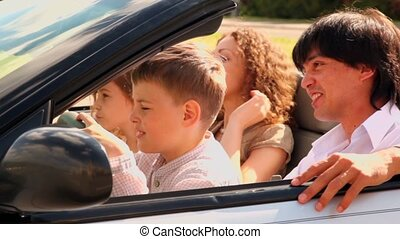 Kids sit on parents lap in cabriolet at sunny summer day