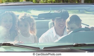 Kids sit on parents lap in cabriolet, view through front window