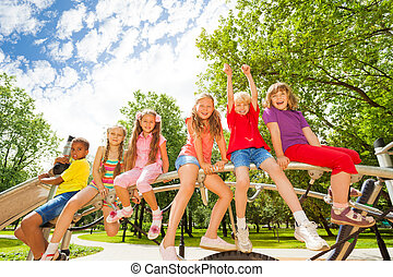 Kids sit on round bar of playground construction
