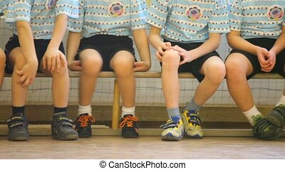 Kids sitting on the bench in the sports hall