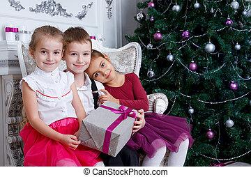 Kids sitting under Christmas magenta tree with gift-box