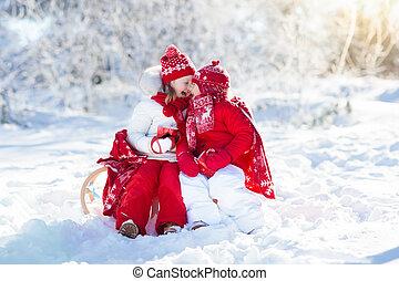 Kids sledding in winter forest. Children drink hot cocoa in...