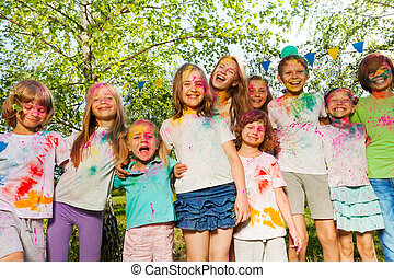 Kids smeared with colored powder standing in a row