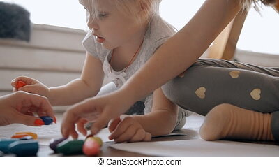 Kids spending free time together lying on the floor and draw...