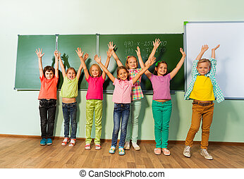 Kids stand with arms up in line near the blackboard during mathematics class and smile