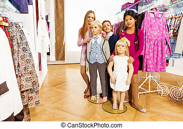 Kids standing with two mannequins in shop