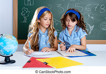 kids students in classroom helping each other at school desk