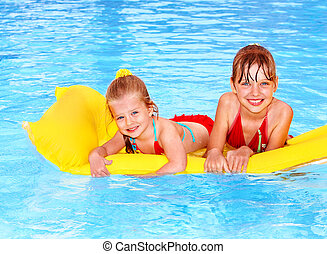 Kids swimming on inflatable beach mattress.