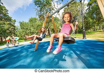 Kids swing on playground