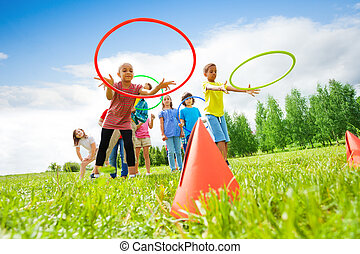 Kids throw colorful hoops on cones while competing - Kids ...