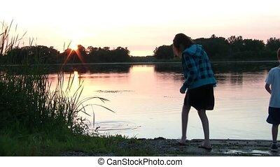 Kids Throwing Rocks Into Calm Lake