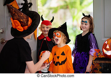 Kids trick or treat on Halloween night. Child and mother at decorated house door. Boy and girl in witch and vampire costume and hat with candy bucket and pumpkin lantern. Woman with sweets.