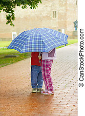 kids under the umbrella - Young girl and boy under a blue...