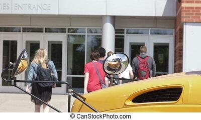 Kids walking to school - High school kids getting off a bus...