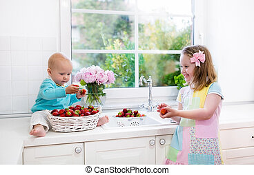 Kids washing strawberry in white kitchen
