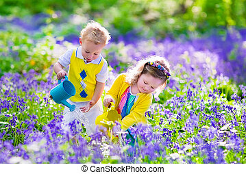 Kids watering flower bed - Kids gardening. Children playing...