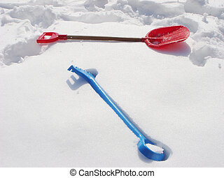Kids winter play objects. Rake and shovel on a snow