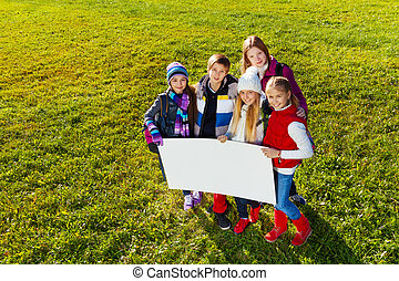 Kids with banner - Group of happy teen kids standing in...