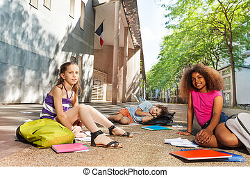 Kids with books on the street get ready for class