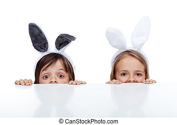 Kids with bunny ears peeking from beneath the table -...